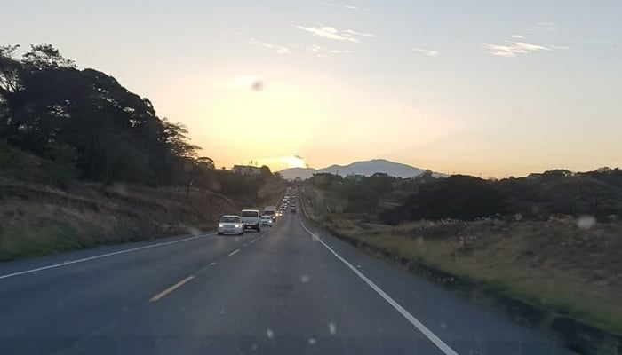 Roads in Central America: Ruta 27 in Costa Rica (with ash plume from volcano in background)