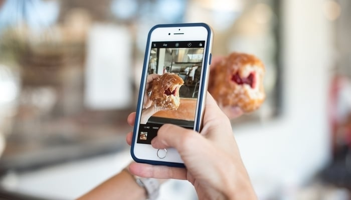 Social media in Guatemala / A person taking a photo of a jam-filled donut with an iPhone